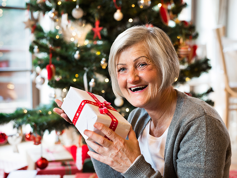 Senior woman holding present in front of Christmas tree