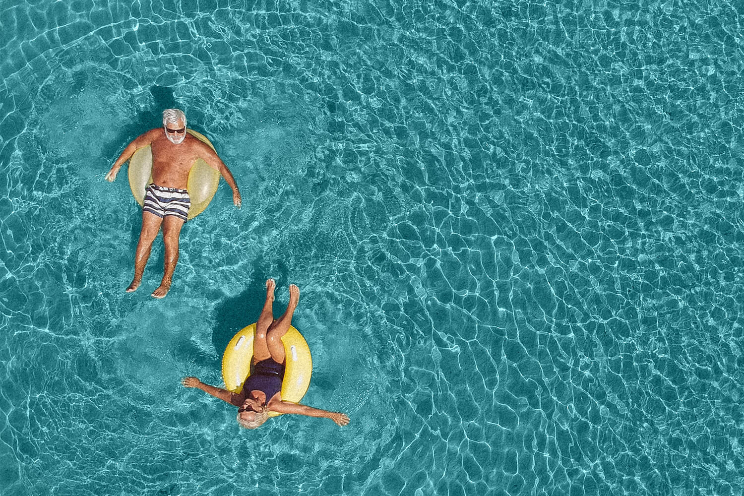 Two people float on rafts in a pool