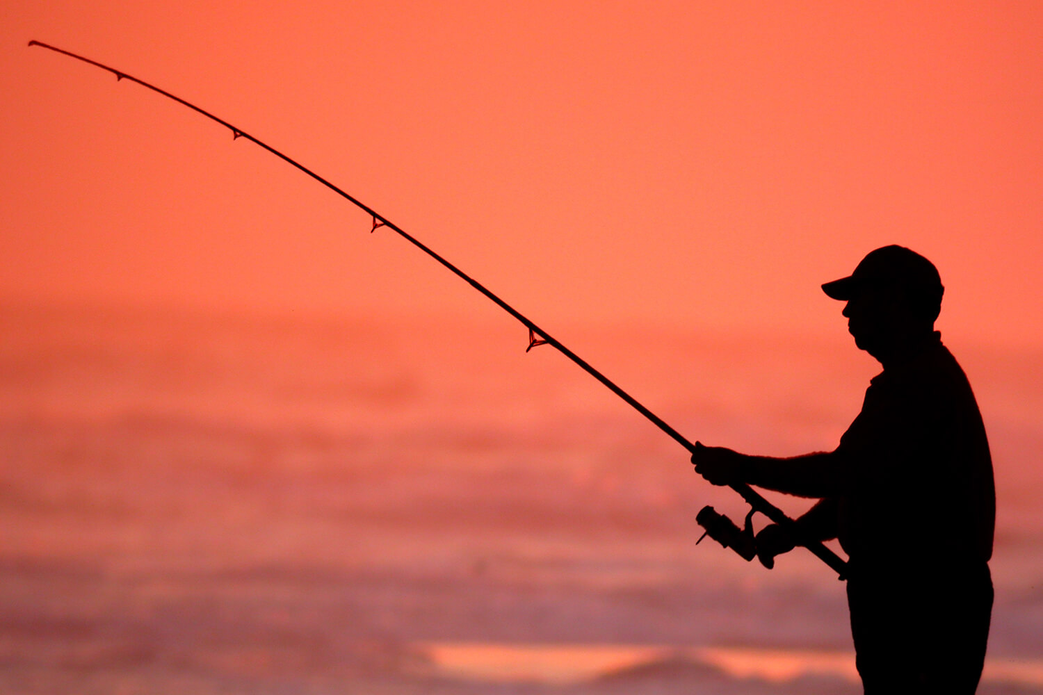 A man goes fishing against the sunset
