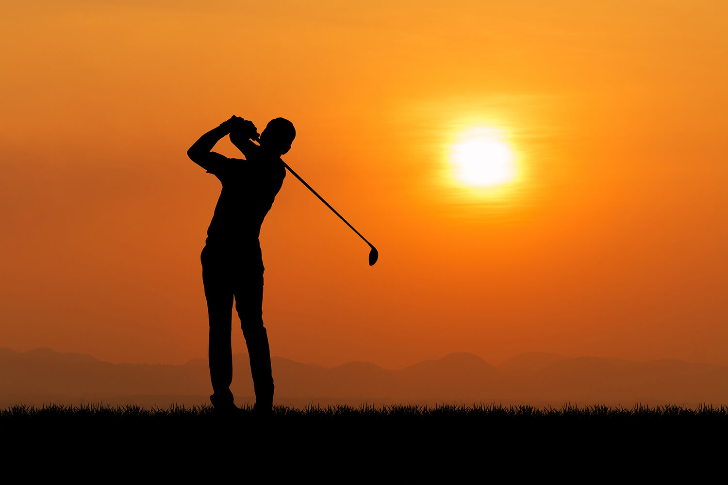 A man swings his golf club into distance